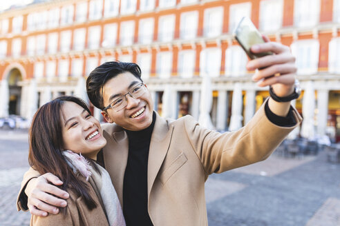 Spain, Madrid, happy young couple taking a selfie in the city - WPEF01477