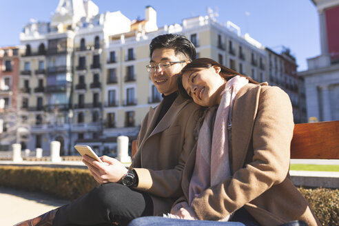 Spain, Madrid, young couple resting on a bench and using cell phone in the city - WPEF01498