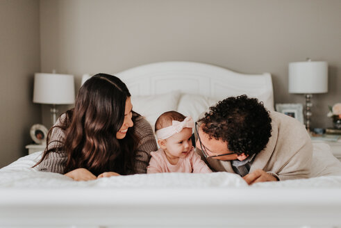 Couple with baby daughter on bed in bedroom - ISF21119