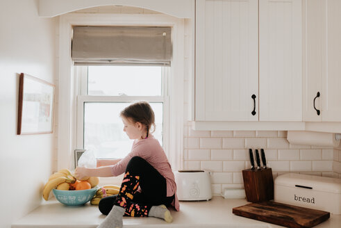 Girl arranging fruits in basket on kitchen worktop - ISF21194