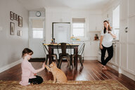 Mother watching daughter play with cat at home - ISF21197