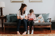 Mother watching daughter play on couch - ISF21203
