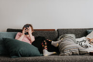 Girl playing with smartphone on couch - ISF21206