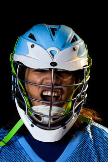 Young male lacrosse player in lacrosse helmet shouting, close up portrait against black background - ISF21224