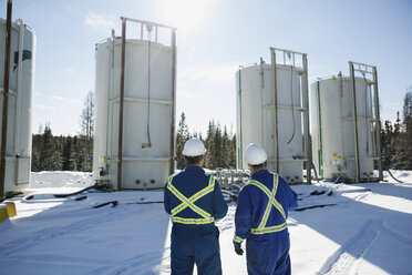 Male workers looking up storage tanks in snow - HEROF35600