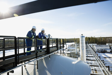 Male workers on platform overlooking gas plant - HEROF35612