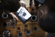 Overhead entrepreneurial coffee roasters using digital tablet - HEROF35615
