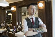Pensive tattooed barber looking away in barber shop - HEROF35627