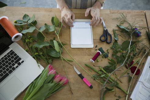 Overhead view florist using digital tablet - HEROF35630
