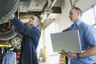 Mechanics with laptop under car auto repair shop - HEROF35633