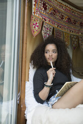 Pensive young woman writing in journal at bedroom window - HEROF35657