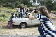 Man photographing young women sitting on top of car - HEROF35660