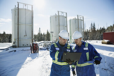Male engineers using laptop at snowy gas plant - HEROF35717