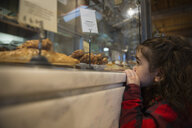 Girl eyeing pastries in bakery display case - HEROF35726