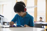 Focused boy using digital tablet with headphones counter - HEROF35747