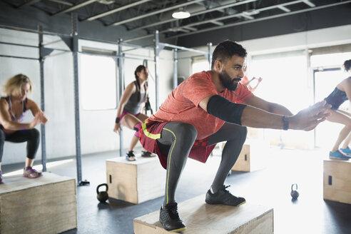 Focused man jump squats in crossfit exercise class - HEROF35801
