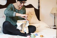 Woman embroidering sitting on bed at home - IGGF01021