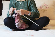 Close-up of woman embroidering sitting on bed at home - IGGF01024