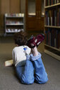 Female student reading book in a public library - IGGF01042
