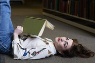 Female student reading book in a public library, lying on the ground - IGGF01060