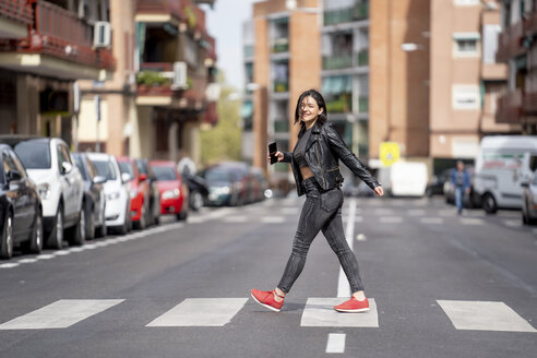 Young woman crossing the pedestrian crossing and using mobile phone - OCMF00384