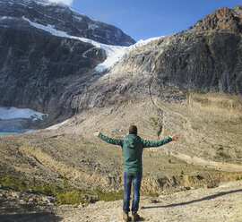 Canada, Jasper National Park, Hiker  with raising arms at Mount Edith Cavell and Angel Glacier - EPF00589