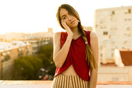 Portrait of teenage girl on roof terrace in the city at sunset - ERRF00940