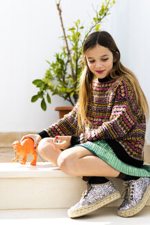 Girl playing with dinosaur toy at home - ERRF00967