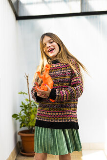 Portrait of happy girl playing with dinosaur toy at home - ERRF00970