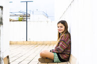 Portrait of smiling girl sitting on roof terrace - ERRF00976