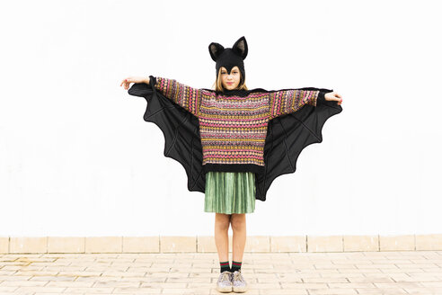 Portrait of girl in bat costume spreading wings in front of white wall - ERRF00988