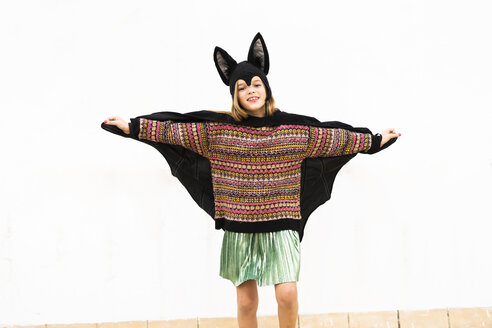 Portrait of girl in bat costume spreading wings in front of white wall - ERRF00991