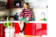 Girl playing with microphone and smartphone in kitchen at home - ERRF00997