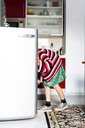 Girl in striped pullover in kitchen at home looking in fridge - ERRF01000