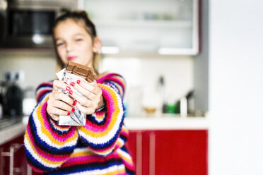 Girl in striped pullover in kitchen at home eating chocolate - ERRF01003