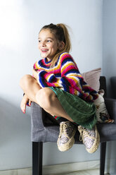 Happy girl in striped pullover sitting on chair at home - ERRF01006