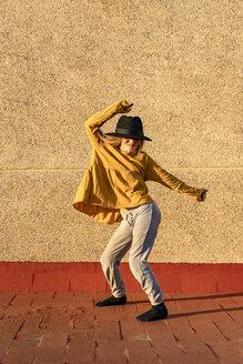 Girl wearing oversized hat dancing on root terrace - ERRF01015