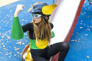 Girl in super heroine costume on playground slide flexing muscles - ERRF01024