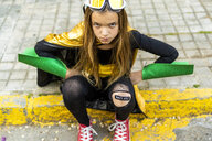 Girl posing in super heroine costume sitting on curb - ERRF01045