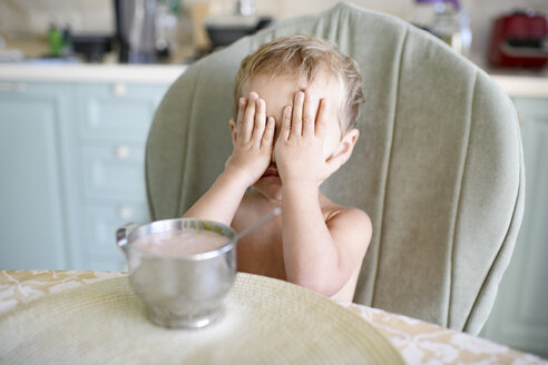 Little girl at dining table covering her eyes - EYAF00141