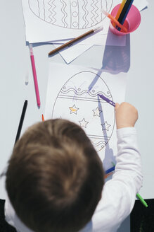 Top view of toddler coloring Easter egg on a paper - MOMF00678