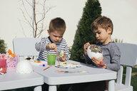 Friends painting Easter eggs in garden - MOMF00687