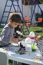 Friends painting Easter eggs in garden - MOMF00690