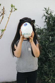 Girl holding painted Easter egg in garden covering her face - MOMF00693