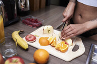 Close-up of young woman cutting fruit in kitchen - IGGF01080