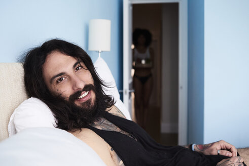Portrait of smiling tattooed man lying n bed with girlfriend in background - IGGF01095