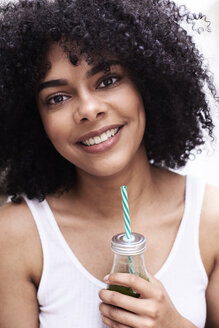 Portrait of smiling beautiful young woman holding green healthy smoothie - IGGF01098