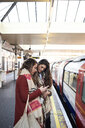 UK, London, two women using cell phone at underground station platform - IGGF01104