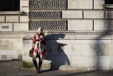 Stylish woman standing at a building using cell phone - IGGF01122