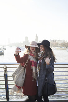 UK, London, two women taking a selfie on Millennium Bridge with cityscape in background - IGGF01137